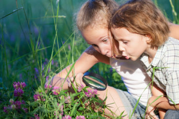 Image of two happy children looking at flowers through a magnifying glass in the park. Concept Brother And Sister Together Forever