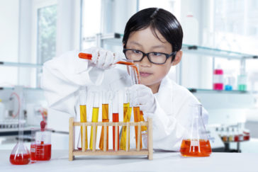 Image of cute little scientist doing research with chemical fluid in the laboratory