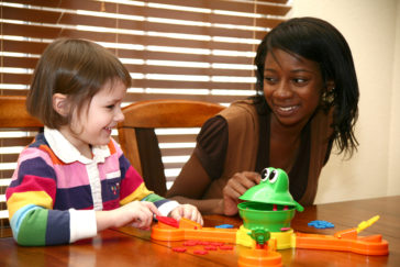 Beautiful african american woman playing games with 5 year old girl.