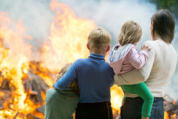 Image of Mother with children at burning house background
