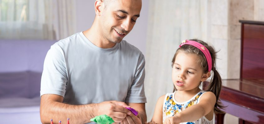 Little girl & her father playing with putty