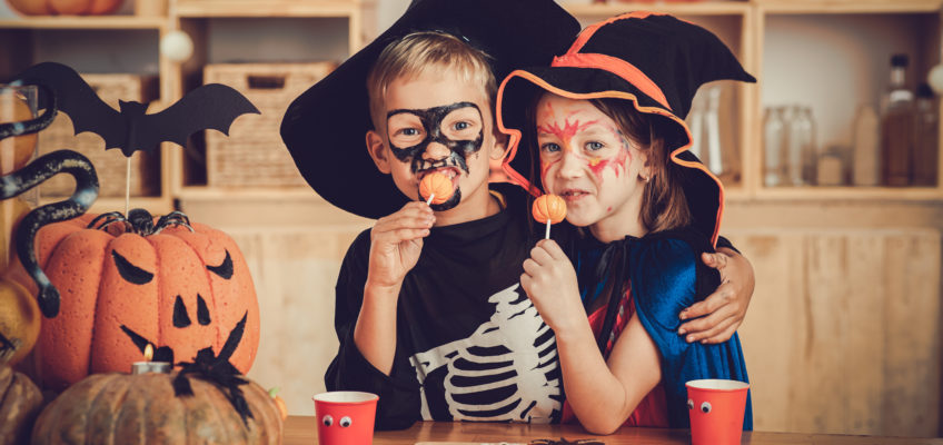 Image of hugging boy and girl enjoying sweets at Halloween party
