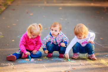 Image of happy children draw with crayons on the pavement in the park