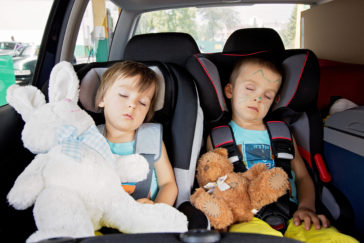 Image of Two kids sleeping in the car with teddy bears