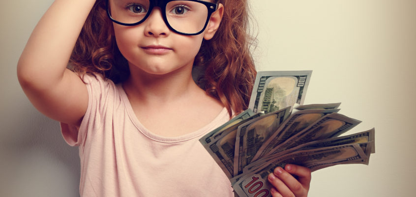 Image of girl in glasses scratchign her head with money in her hand